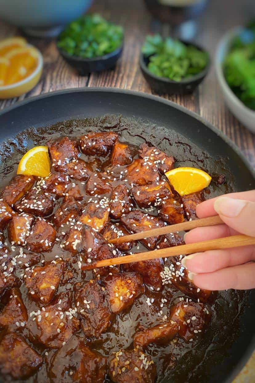 Vegan Orange Tofu Recipe. Chopsticks picking up tofu cube coated in orange sauce.