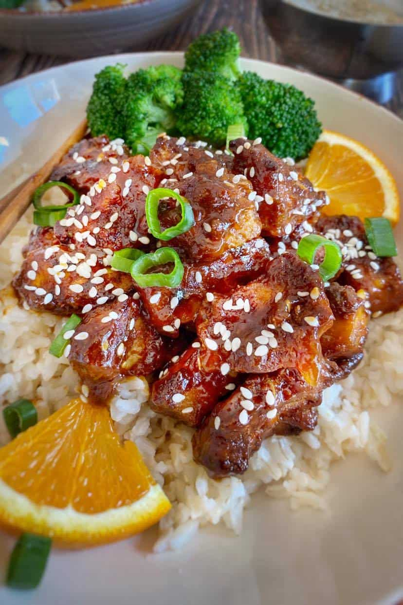 Vegan Orange Chicken with broccoli and brown rice, garnished with fresh oranges.