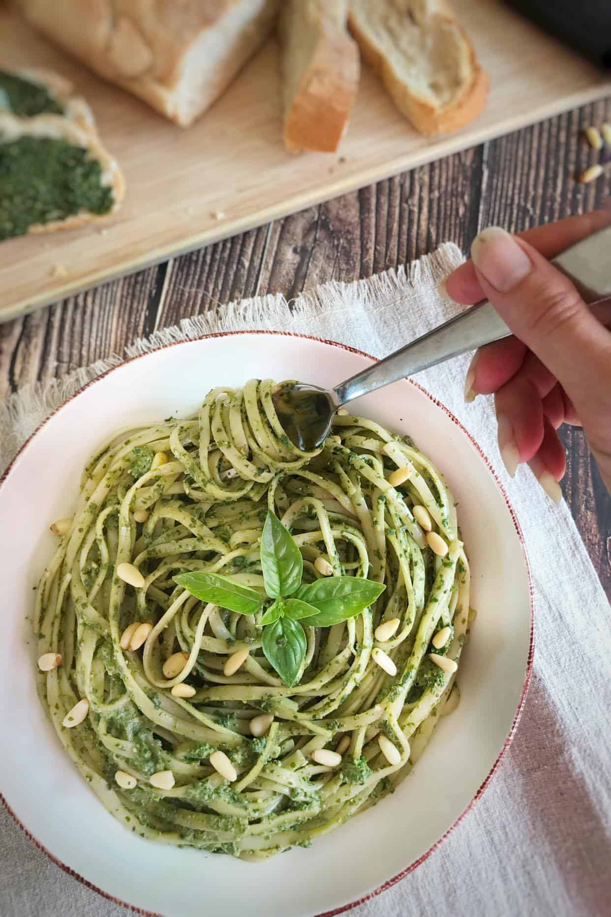 hand turning fork in a bowl of the best vegan pesto