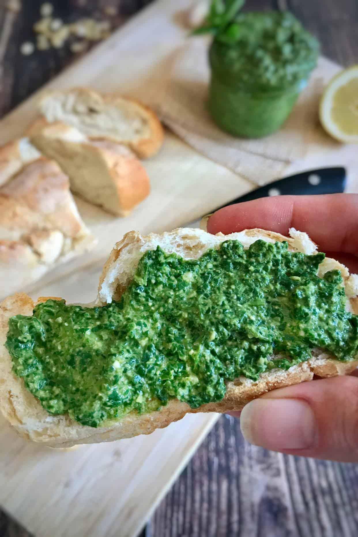 Vegetarian basil pesto spread on slice of bread.