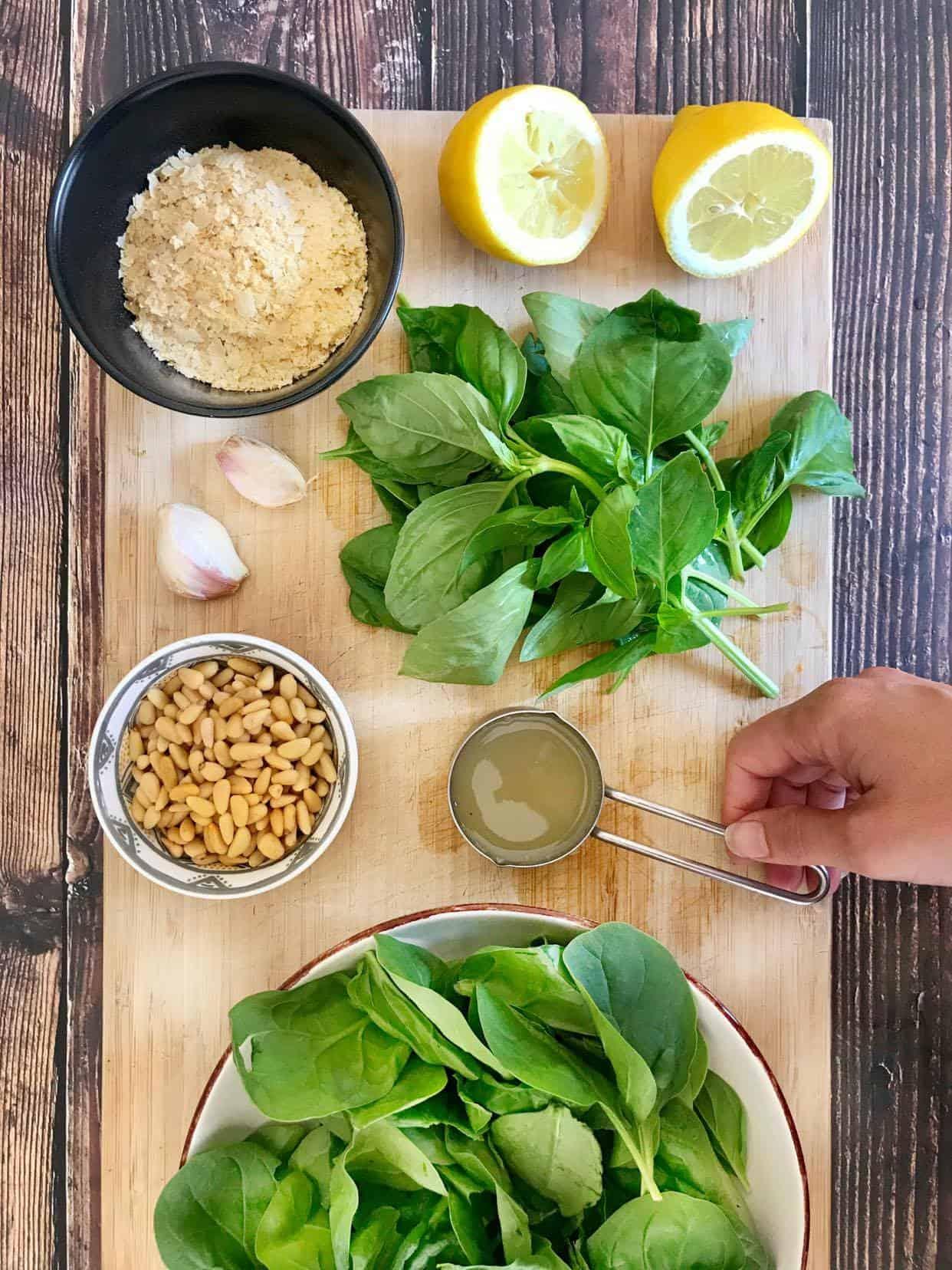 Oil-free vegan pesto ingredients (lemon juice, nutritional yeast, basil, garlic, pine nuts, aquafaba, and spinach).