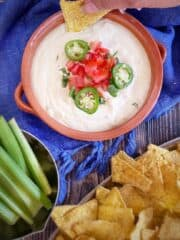 Vegan Cashew Queso in bowl with chips and celery.