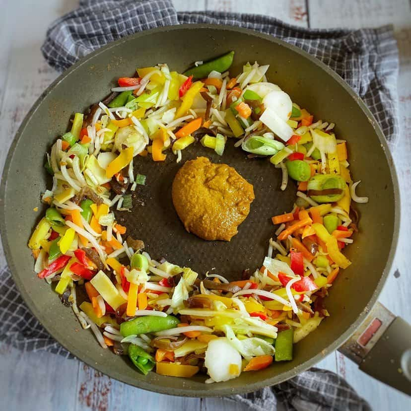 Vegetables and Thai curry paste in a skillet.