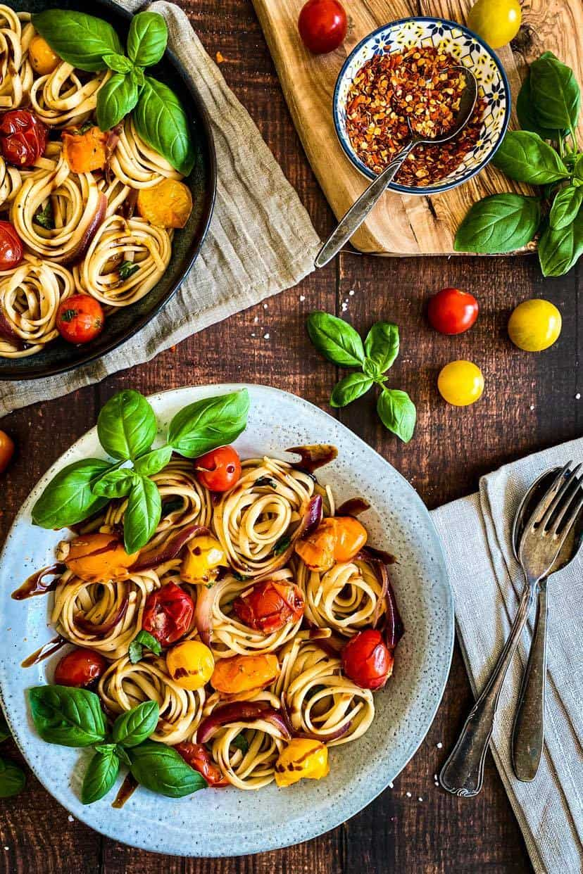 Cherry Tomato & Basil Pasta on two plates with red pepper flakes in a small bowl.