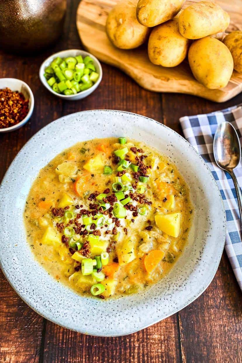 Vegan Potato Soup (creamy and chunky) in bowl with vegan bacon bits and green onion toppings.