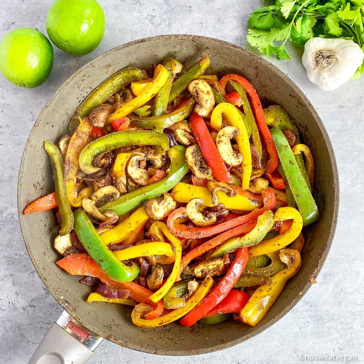 mushrooms added to fajita veggies in skillet