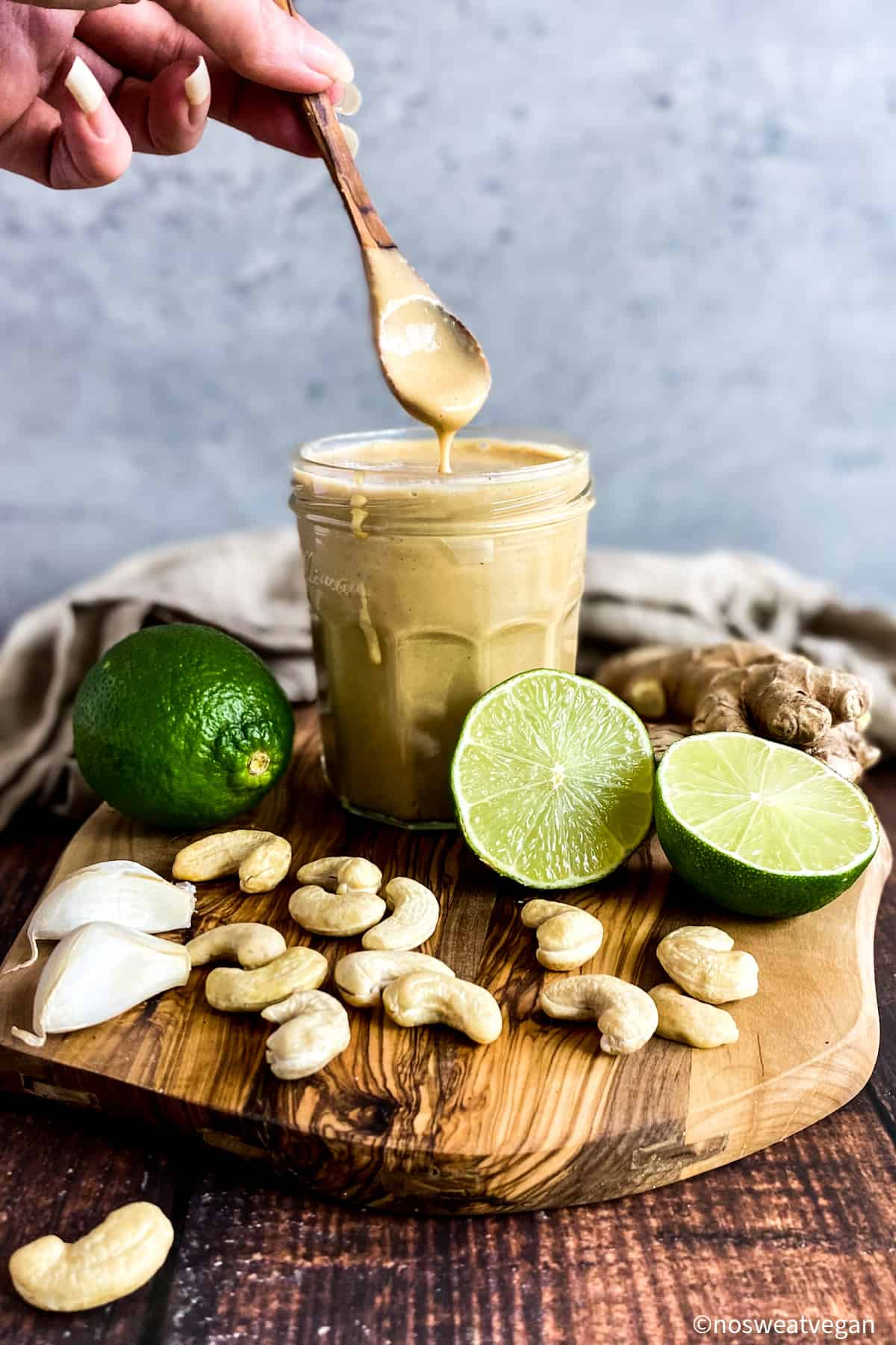 Asian Salad Dressing on a cutting board with limes, ginger, cashews, and garlic.