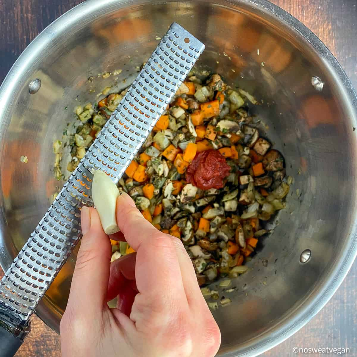 Pot with vegetables and tomato paste. Hand using a Microplane to grate garlic.