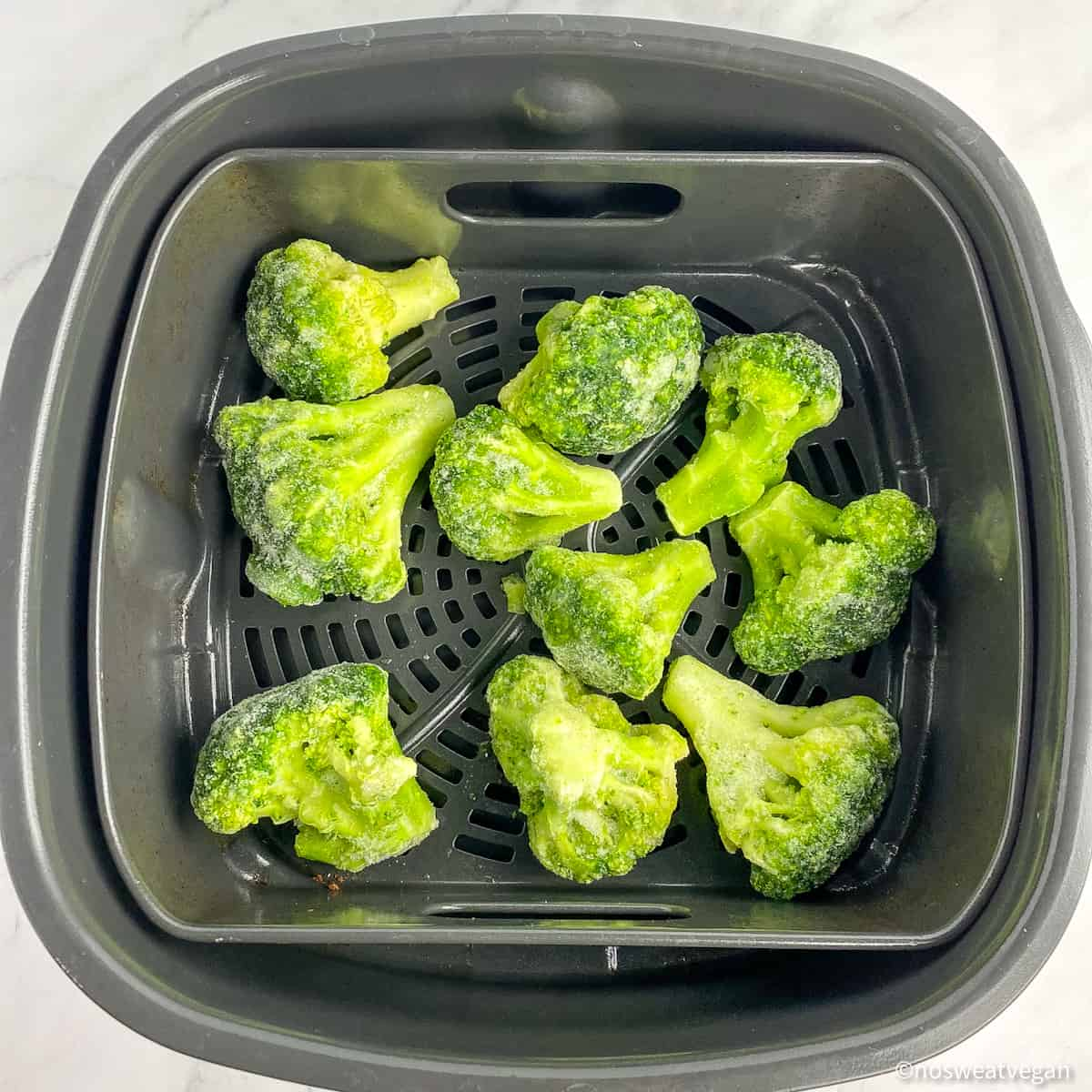 Frozen broccoli in an air fryer basket.
