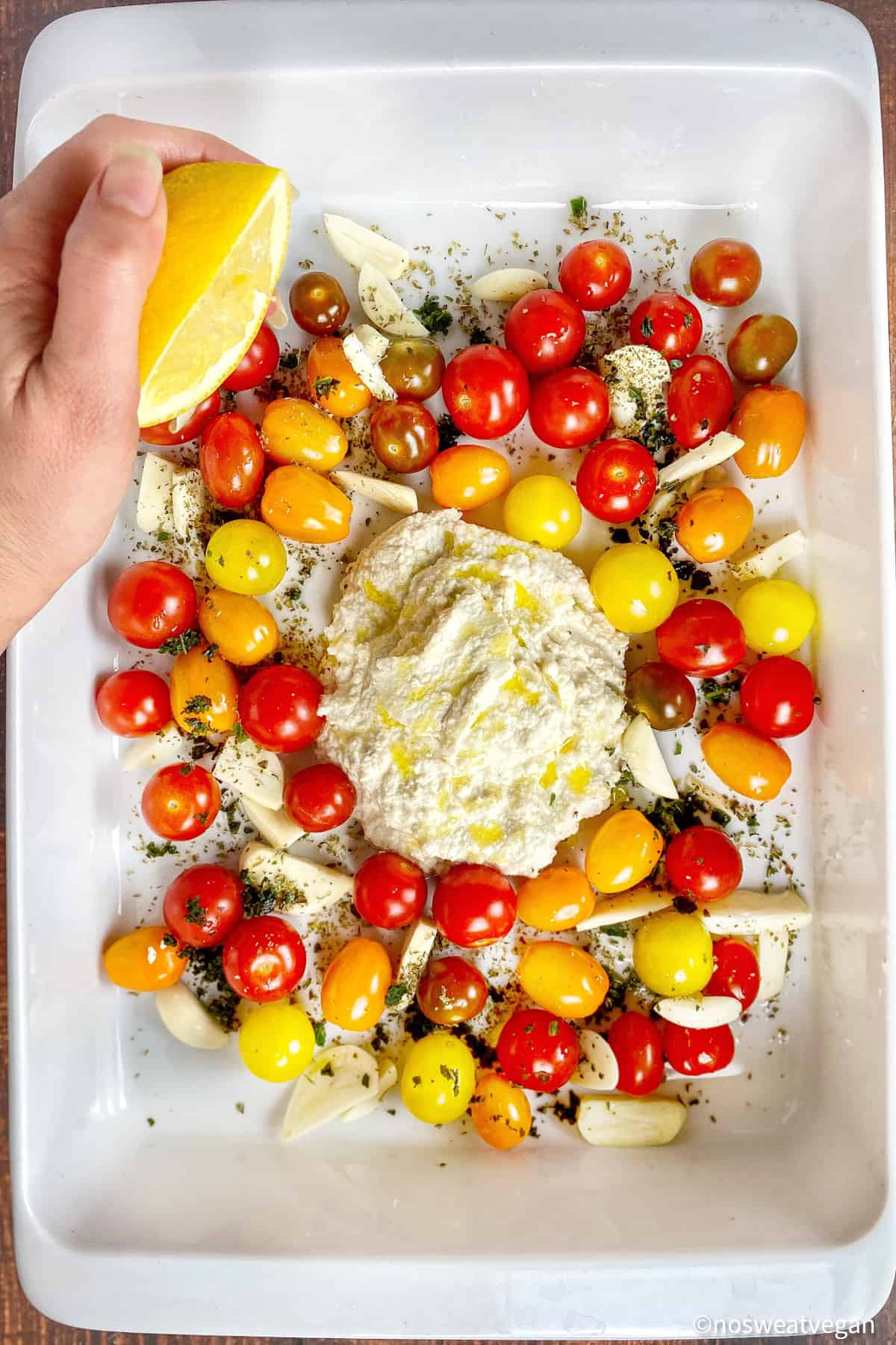Almond ricotta, tomatoes, garlic, and seasoning in a baking dish.