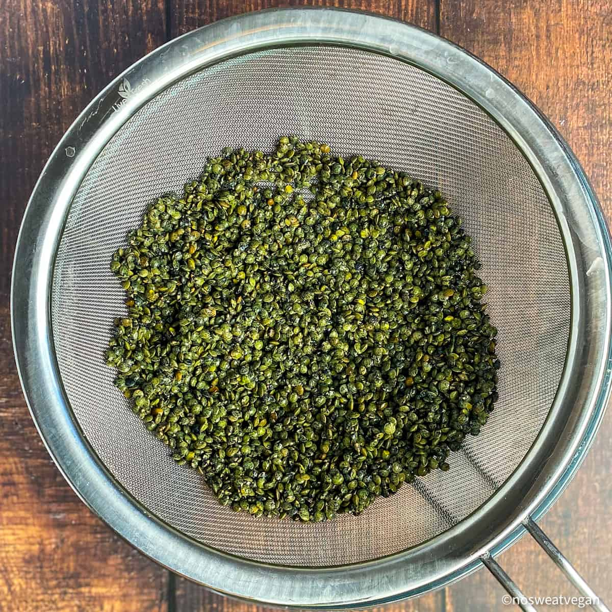 Dried green French lentils in a mesh strainer.