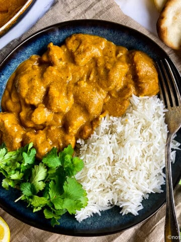 Vegan butter chicken in a bowl with rice and cilantro.