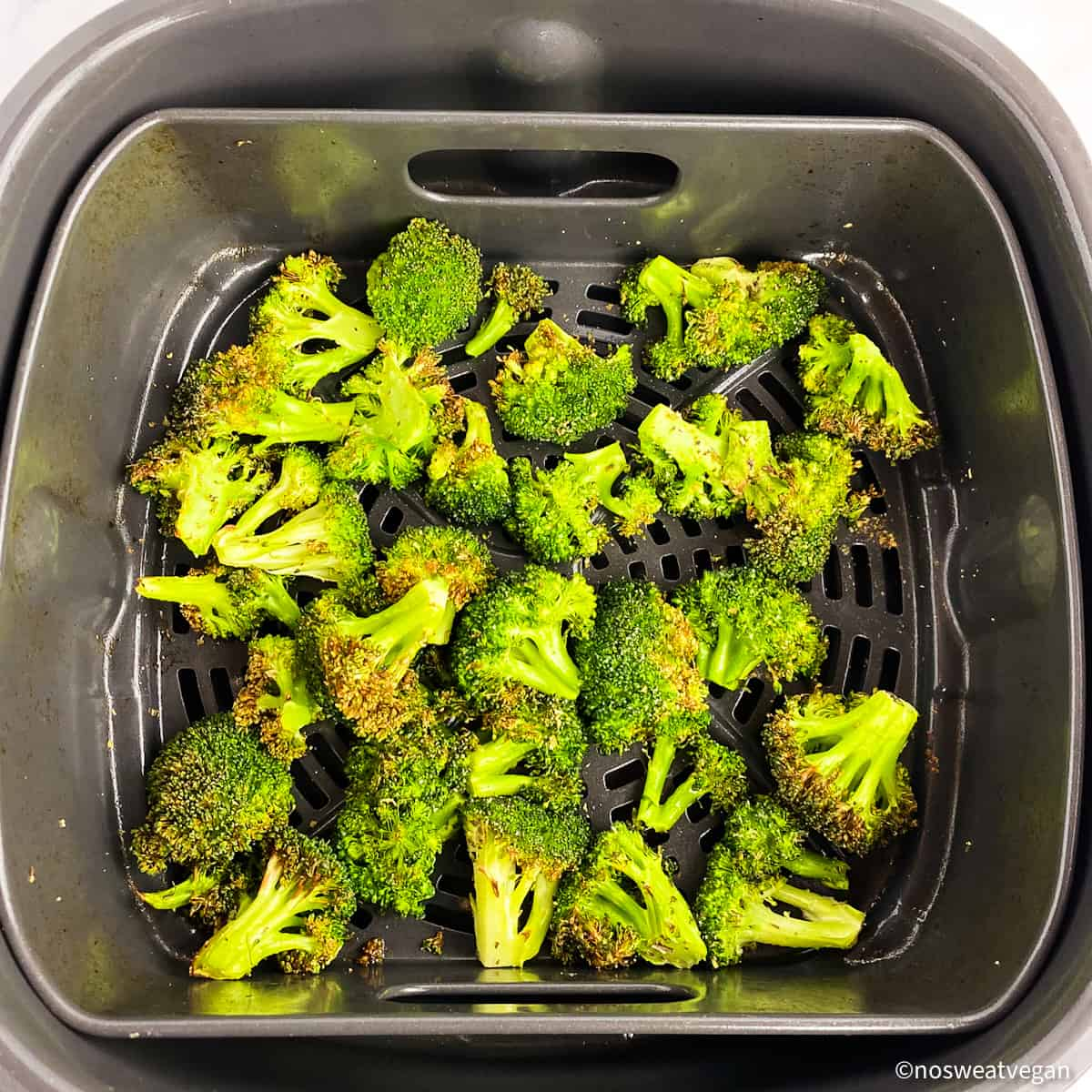 Fresh broccoli roasted in the air fryer basket.