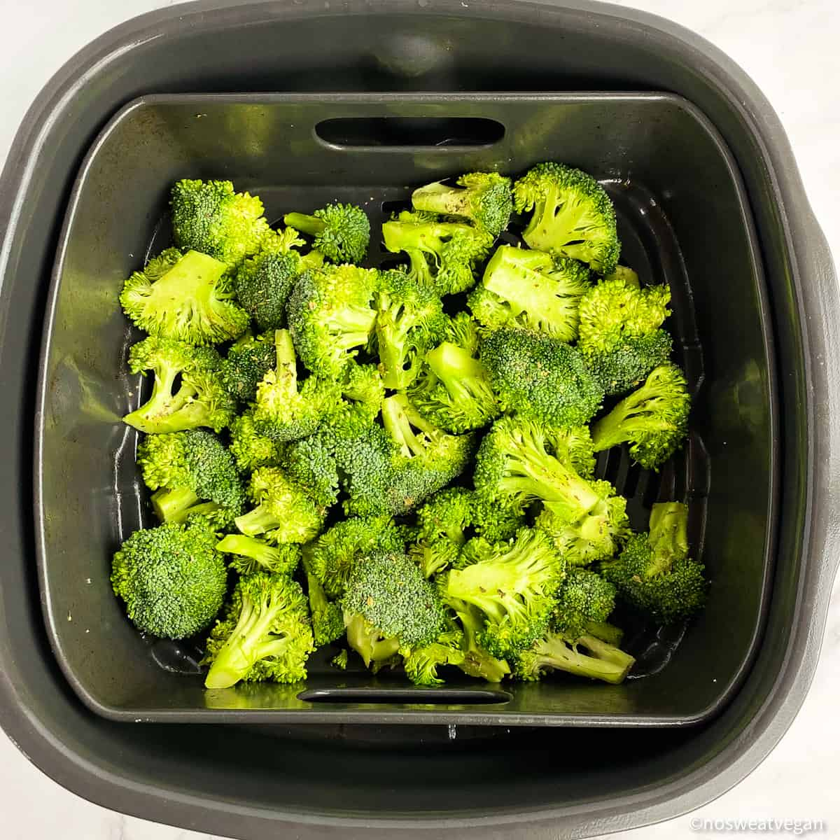Fresh broccoli (uncooked) in the air fryer basket.