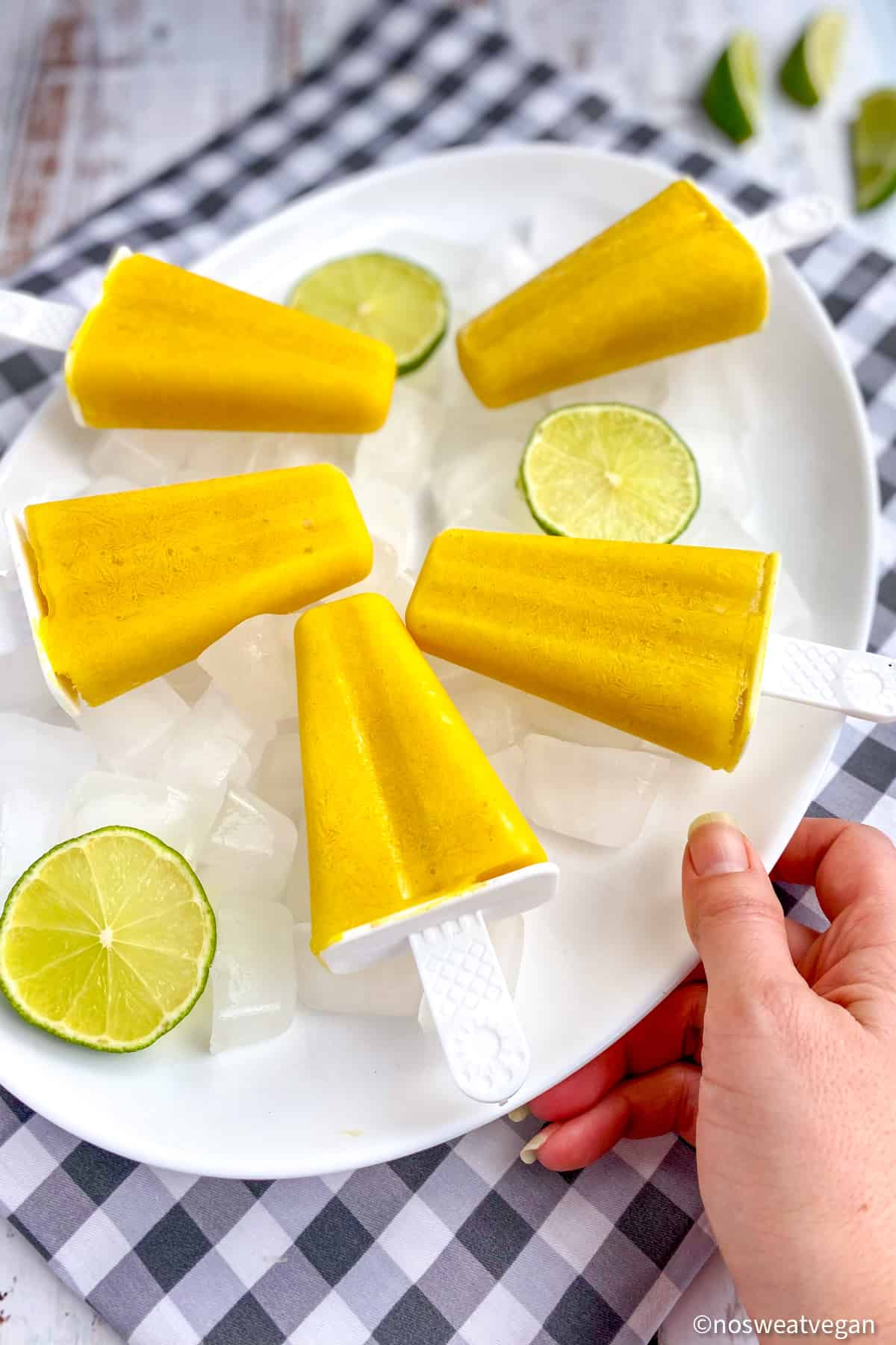 Vegan mango lassi popsicles on a plate with limes.