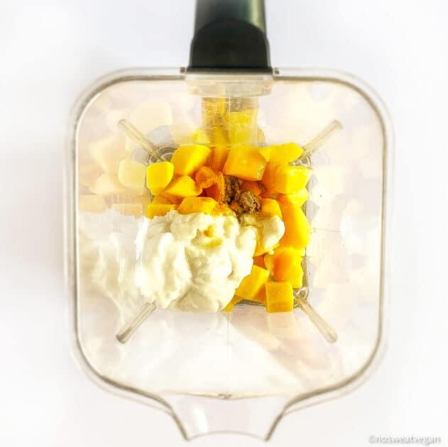 Mango popsicles ingredients in a blender.