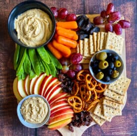 Vegan kids snack board with veggies, hummus, apple slices, cashew butter, graps, pretzels, whole wheat crackers, raisins, and dried apricots.
