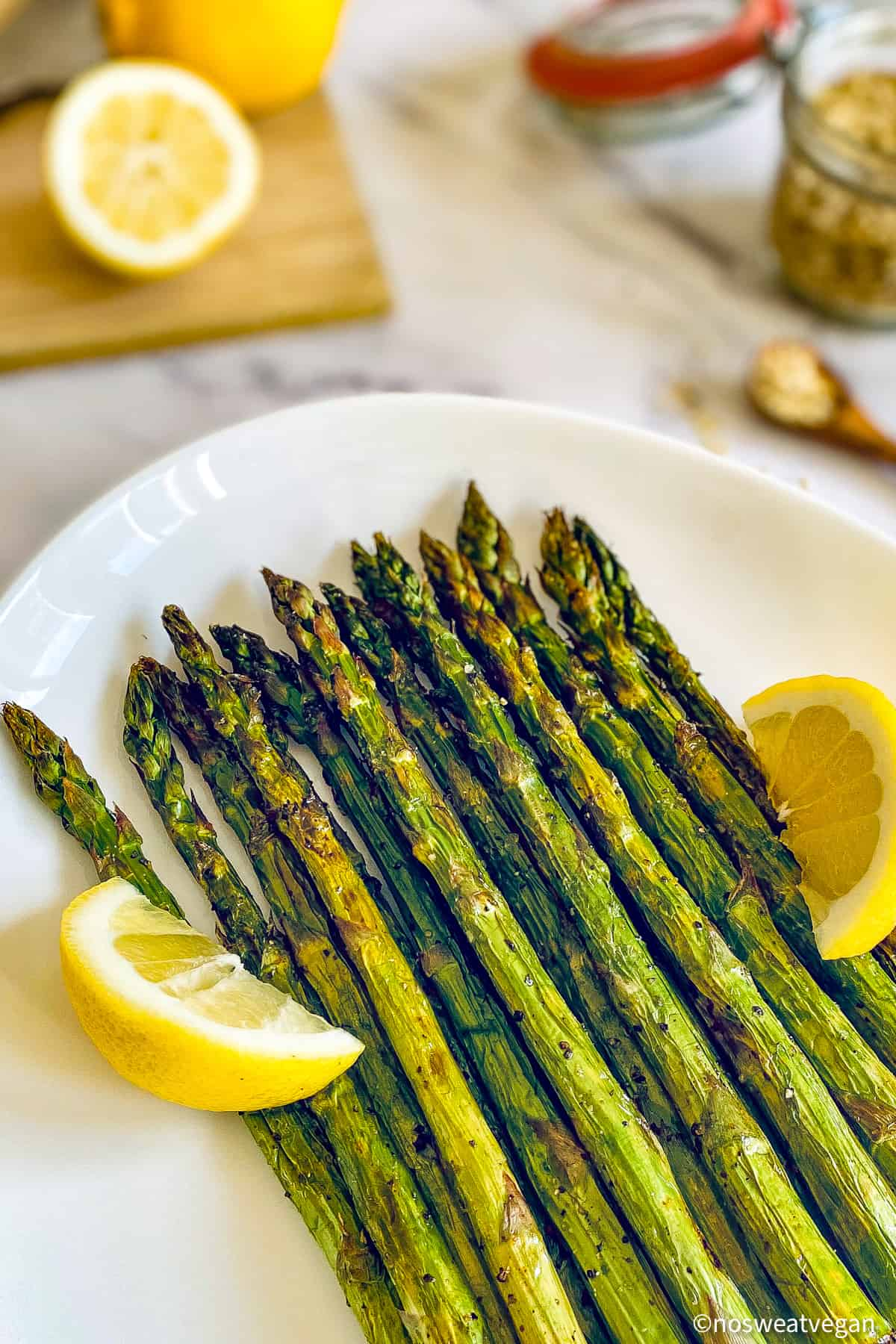 Air fried asparagus on a plate with lemon wedges.