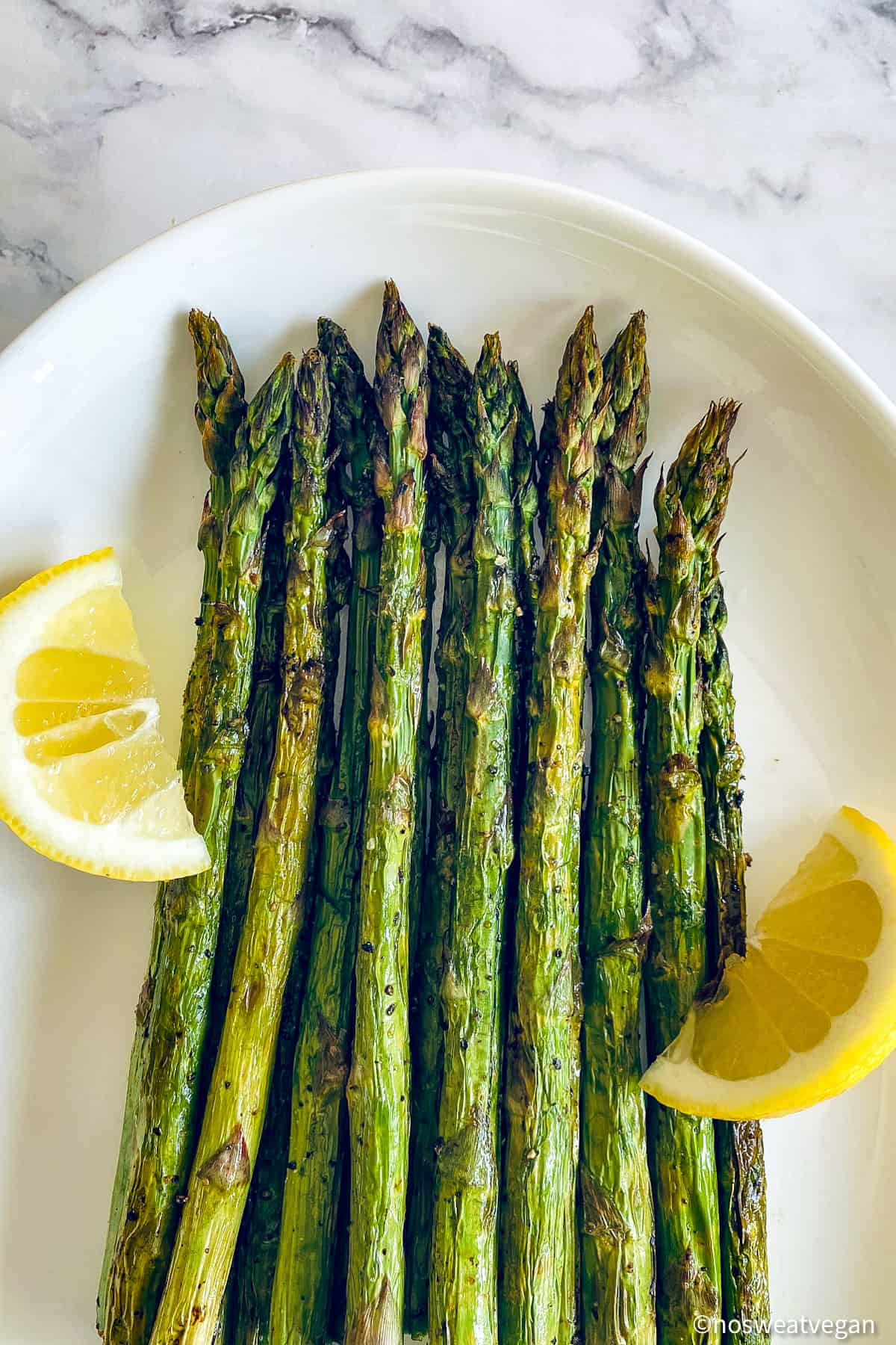 Air fryer asparagus on a plate with lemon wedges.