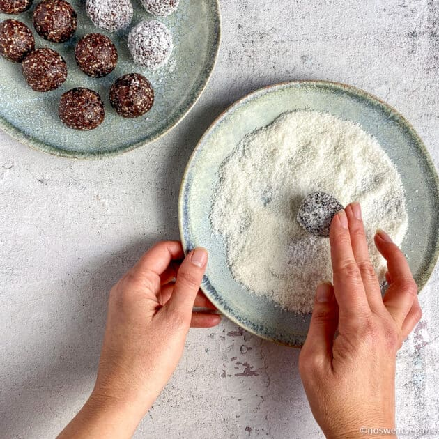 Hand rolling the bliss ball in desiccated coconut.