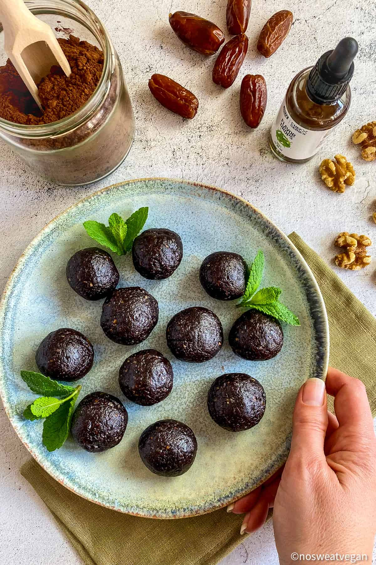 Thin Mint Bliss Balls on plate with mint leaves.