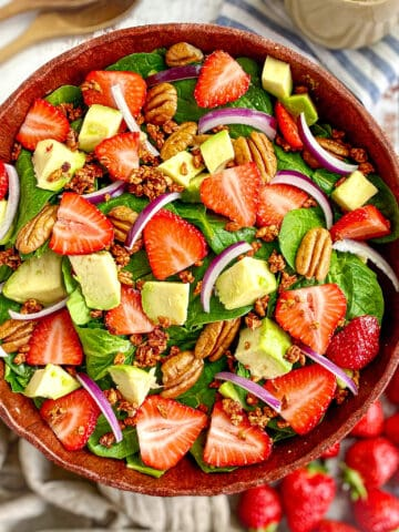 Spinach salad with strawberries, avocado, red onion, pecans, vegan bacon bits, and creamy balsamic dressing.