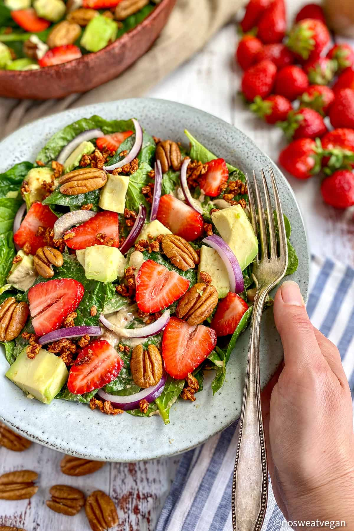 Bowl with vegan spinach strawberry salad.