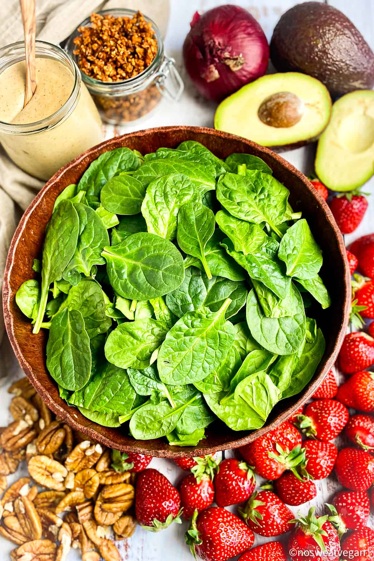 Ingredients for spinach salad with strawberries, avocado, red onion, pecans, vegan bacon bits, and creamy balsamic dressing.
