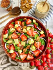 Spinach avocado strawberry salad in bowl with dressing on the side.
