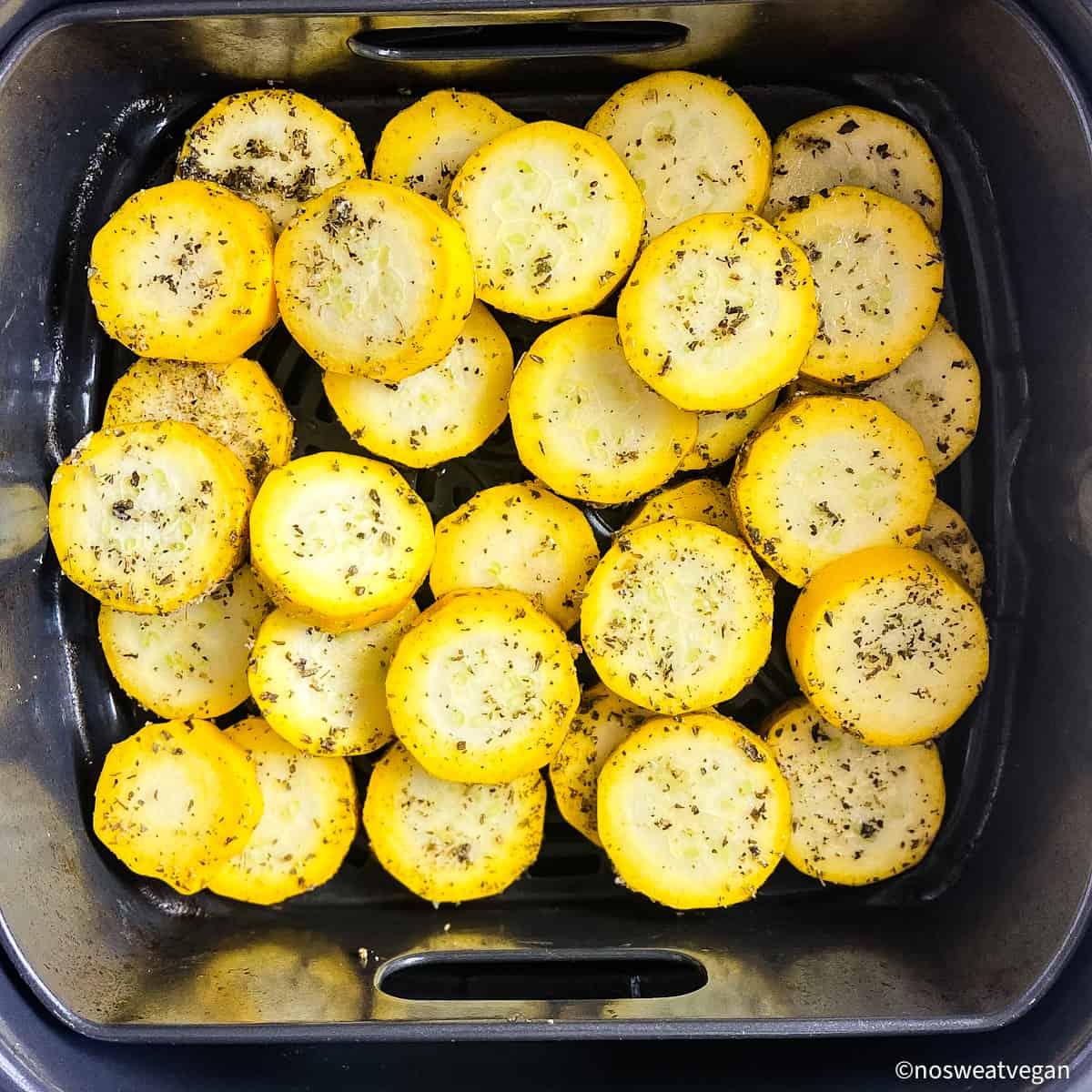 Yellow squash in air fryer basket.