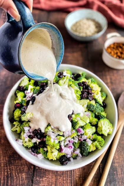Hand pouring cashew dressing on the broccoli salad.