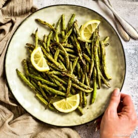 Air fried green beans on plate with lemon wedges.