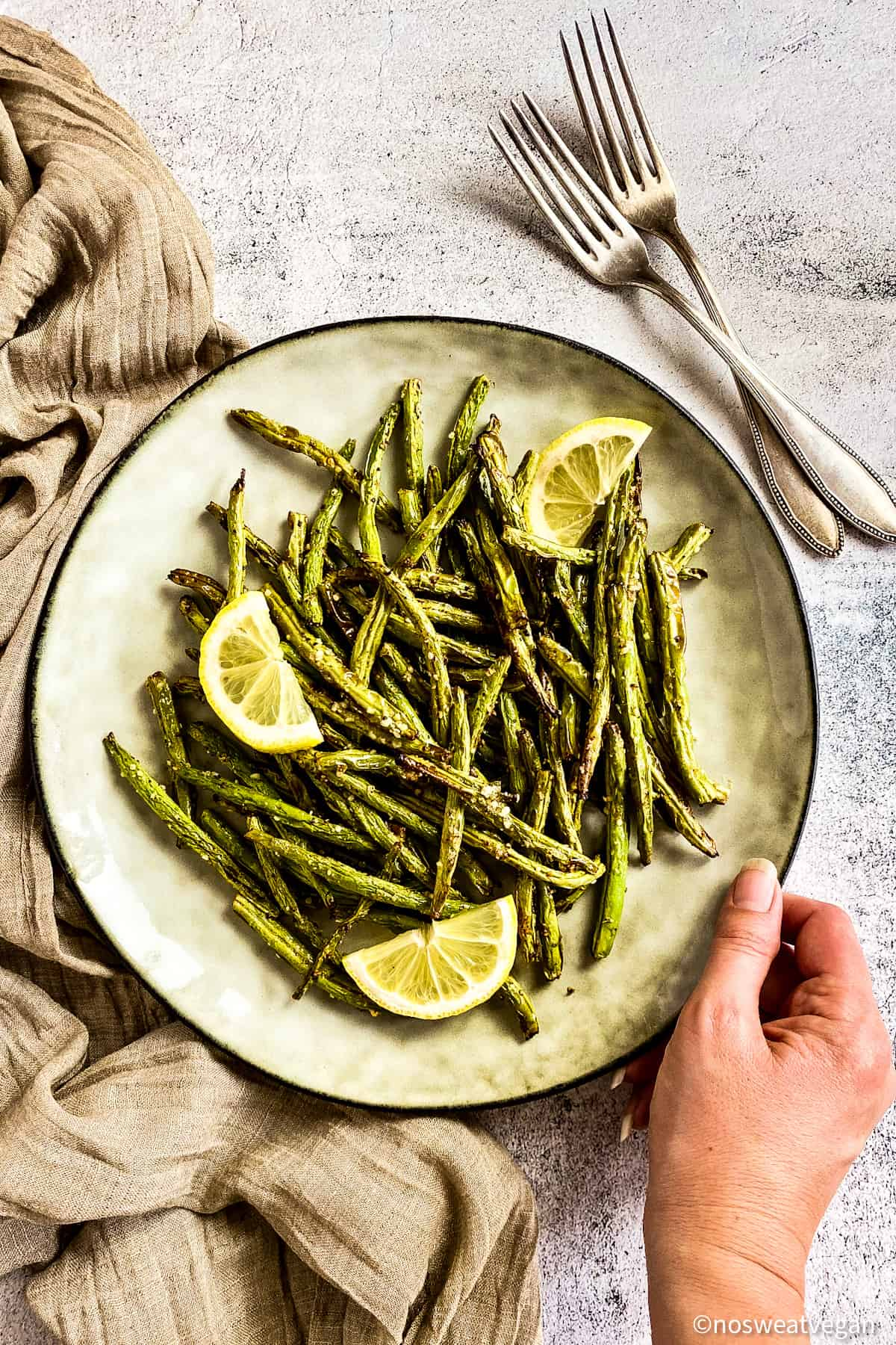 Air fryer green beans on plate with lemon wedges.