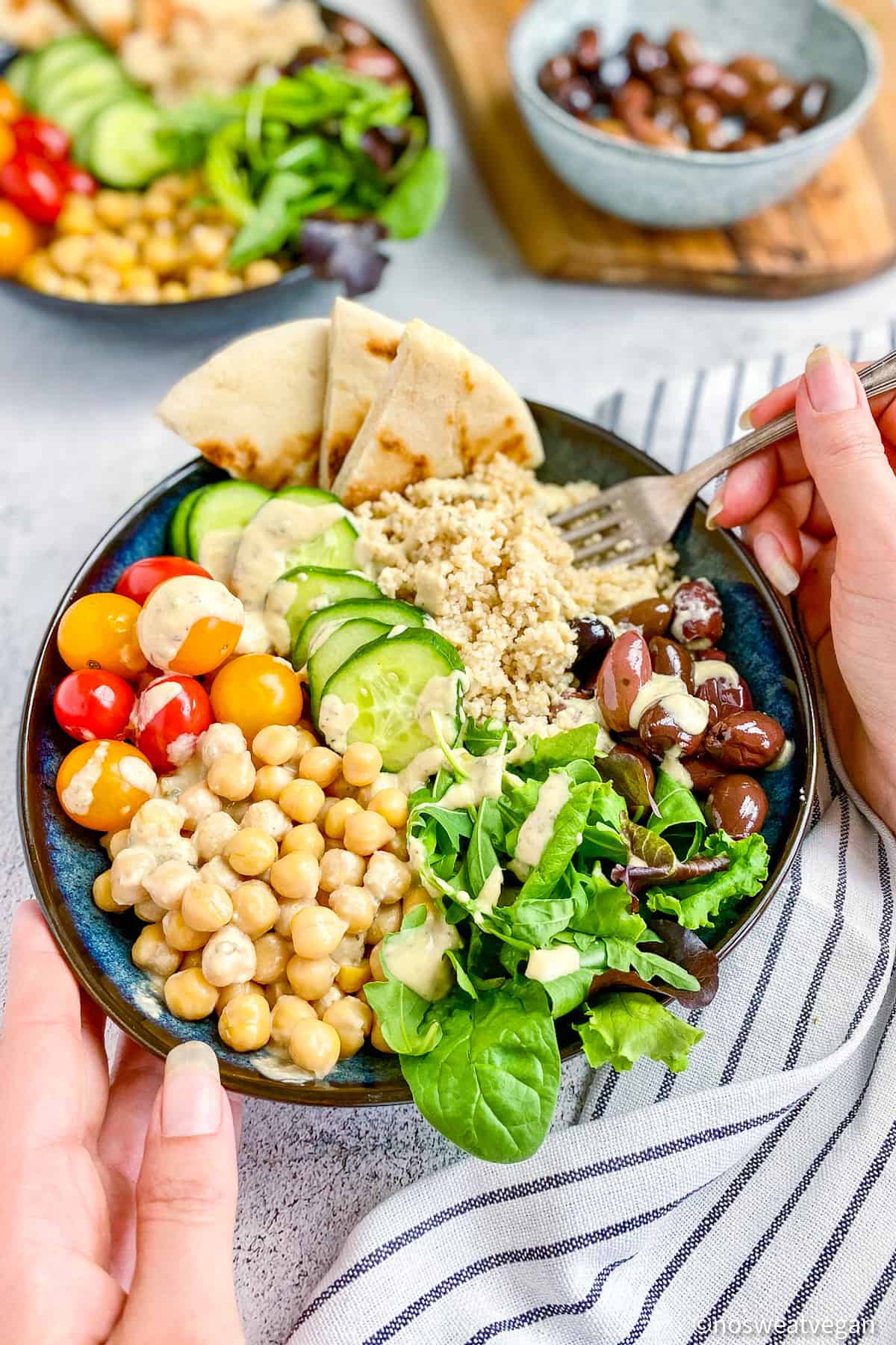 Hands holding chickpea couscous bowl.