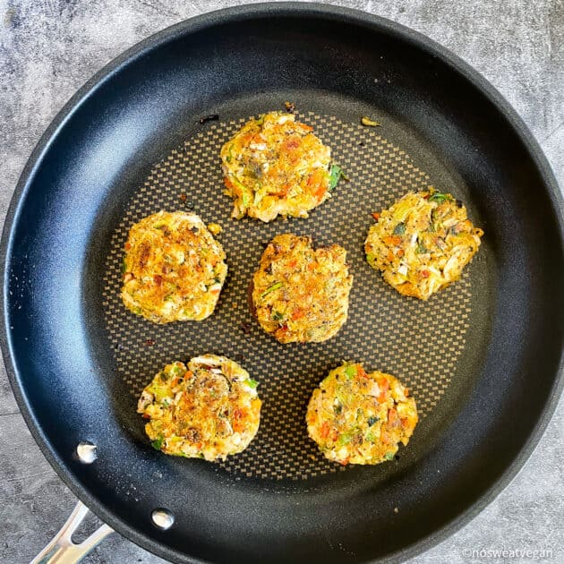 Vegan crab cakes cooked on skillet.