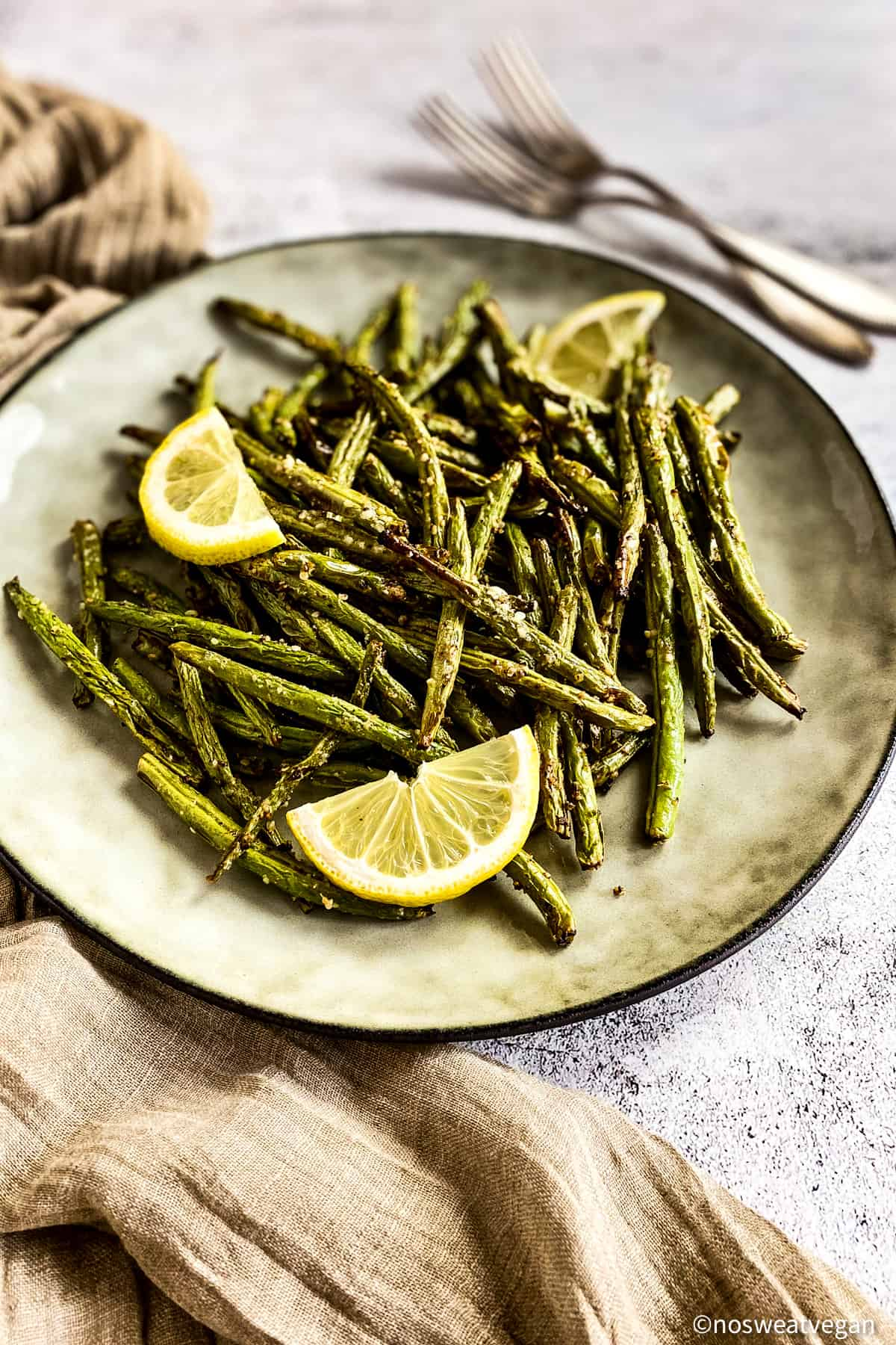 Green beans cooked in the air fryer on plated with lemon wedges.
