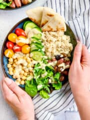 Two hands holding a vegan greek buddha bowl.