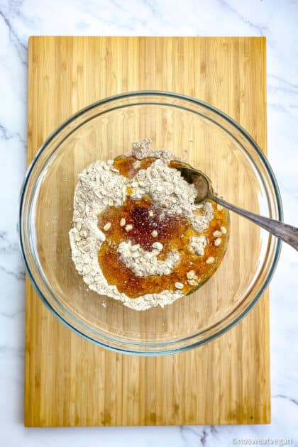 Bowl with flour, oats, maple syrup, and other crumble ingredients.