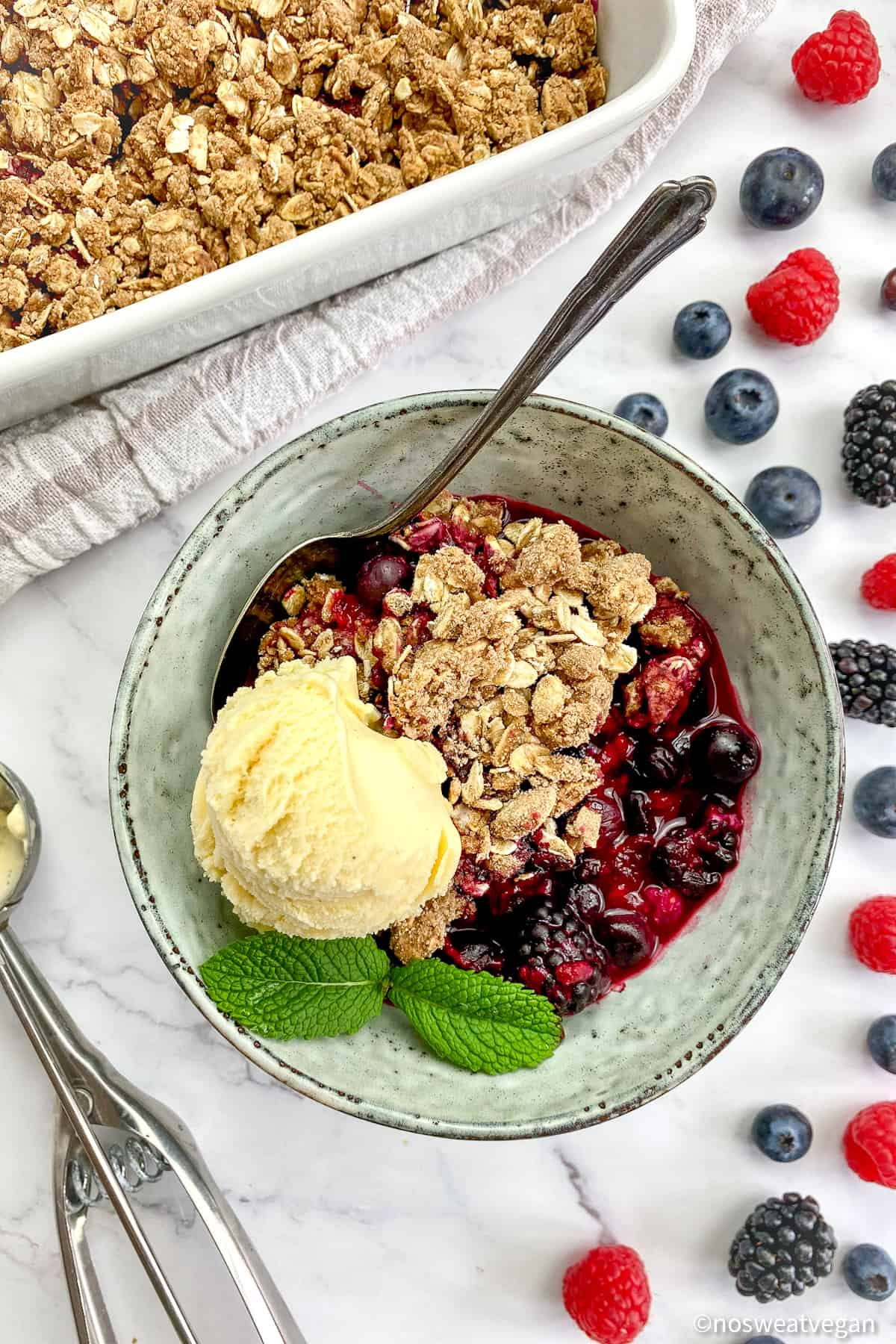 Vegan berry crumble in a bowl with a scoop of ice cream.