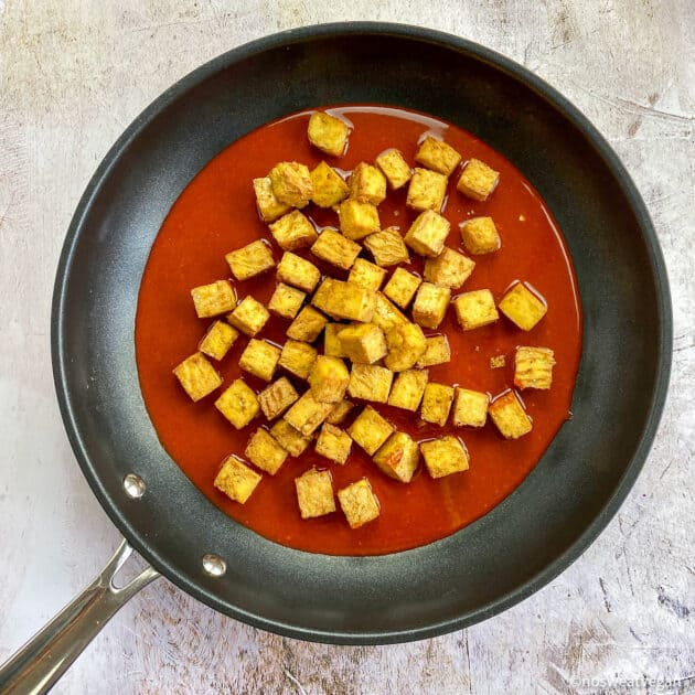 Tofu cubes in skillet with sauce (not mixed).