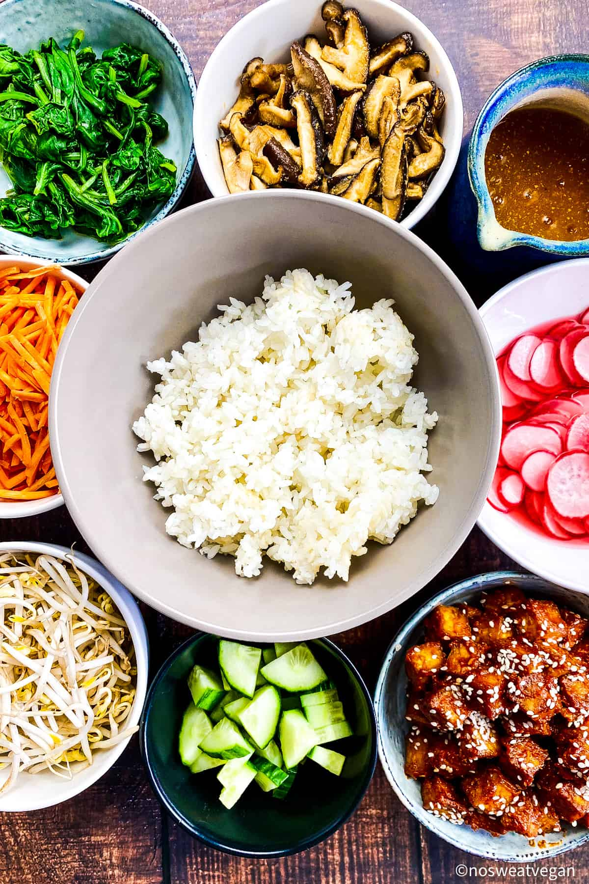 Bowl of rice surrounded by small bowls with the other bibimbap ingredients.