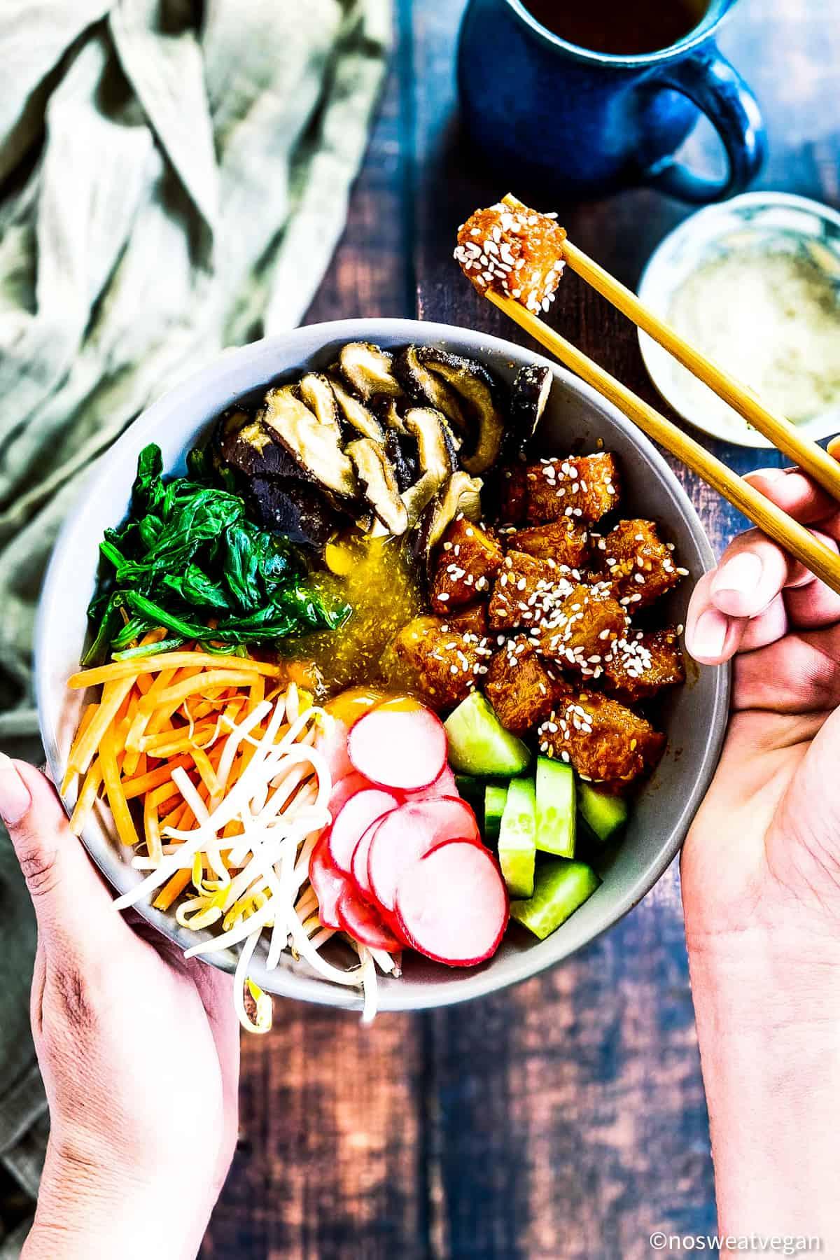 Bibimbap vegan ingredients in bowl with hand holding chopsticks and picking up a piece of Korean tofu.