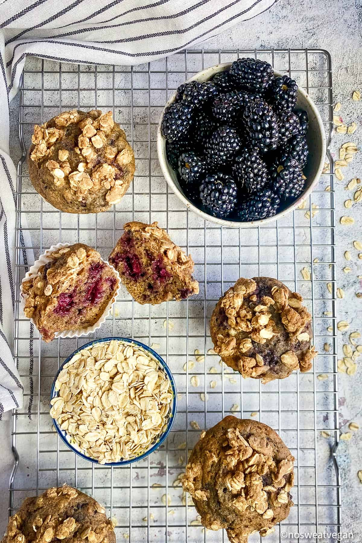 Oil-free blackberry muffins on drying rack with a bowl of blackberries and a bowl of oats.