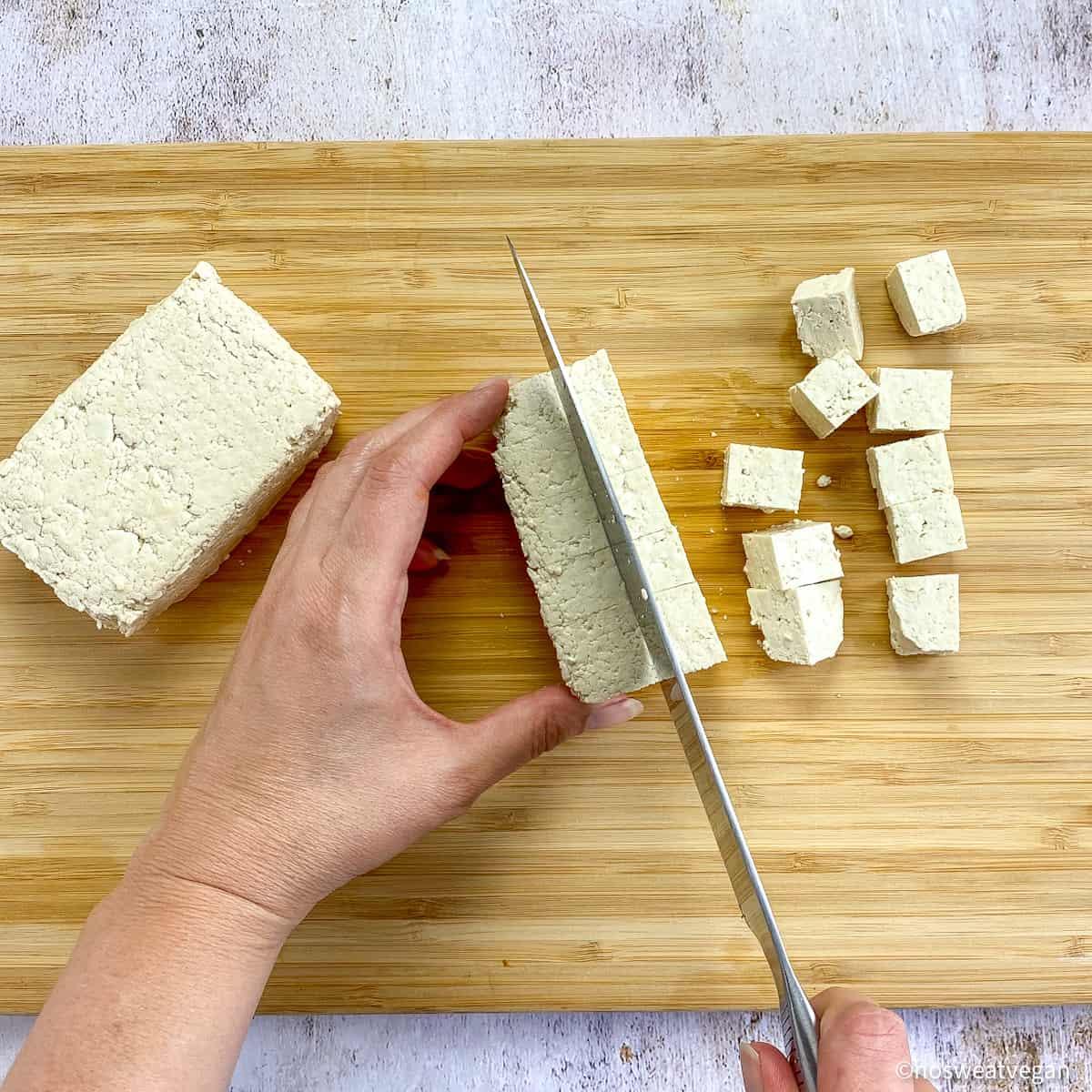 Hands cubing tofu on cutting board.
