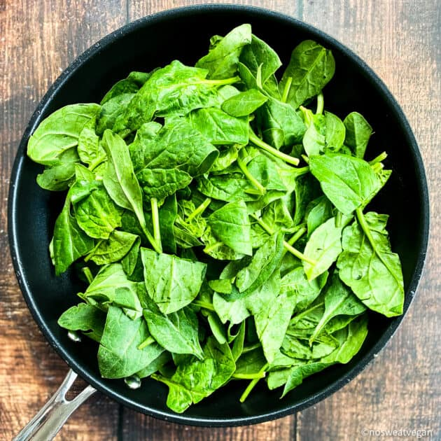 Uncooked spinach in skillet.