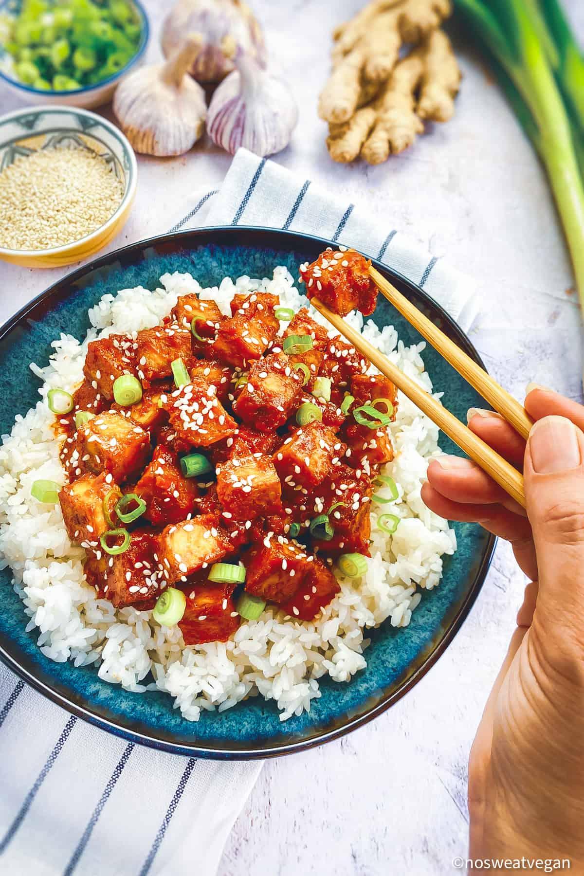 Hand with chopsticks picking up spicy Korean tofu.