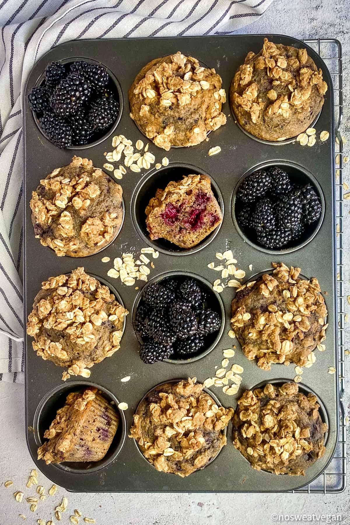 Vegan blackberry muffins in muffin tin with blackberries.
