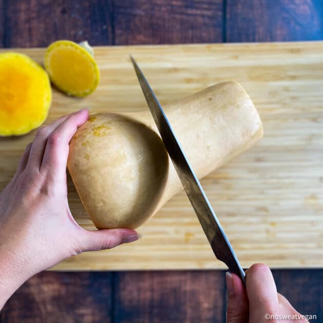 Hand cutting butternut squash in half.