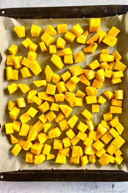 Cubed butternut squash on sheetpan.