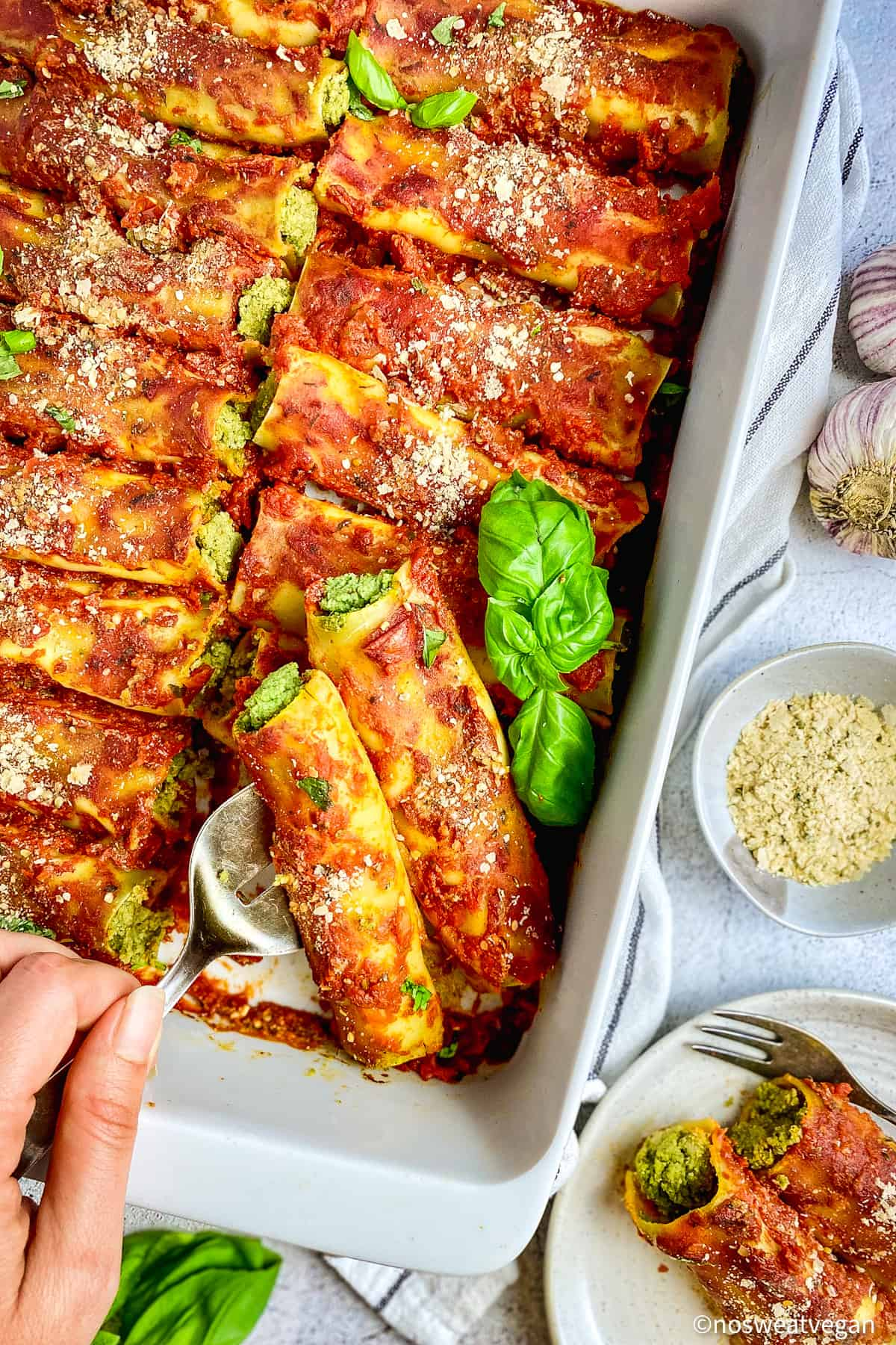 Vegan cannelloni in pan with hand serving.